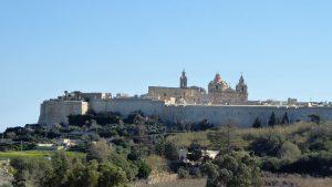 Mdina liegt im Zentrum der Insel Malta auf einem 185 Meter hohen Plateaus, dessen Hänge steil aufragen. Wegen dieser günstigen Lage bauten die Phönizier und die Römer den Ort als Festung aus. Nach der Eroberung im 9. Jahrhundert nannten die Araber den Ort: die von Mauern umgebene Stadt, Mdina.