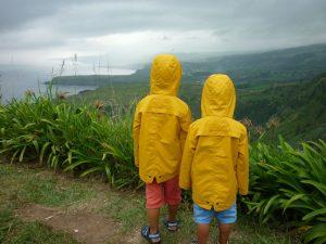 Blick auf die Küste: Kinder mit Regenmantel.