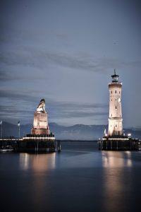"""Löwe und Leuchtturm im Abendlicht. Der """"Lindauer Löwe"""" (links) ist neben dem neuen Leuchtturm das Denkmal, das die Lindauer Hafeneinfahrt charakteristisch prägt. Sie gilt als Wahrzeichen der Stadt und schönste Hafeneinfahrt am gesamten Bodensee. – Foto: Hari Pulko / Lindau-Tourismus"""