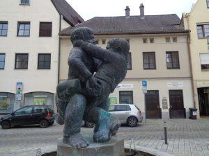 Der kleine Brunnen am östlichen Kirchplatz mit den raufenden Buben symbolisiert den einstigen Konflikt zwischen den zwei Weilheimer Stadtbereichen Untere Stadt und Obere Stadt. – Foto: Dieter Warnick