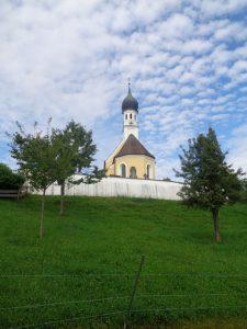 Oberbayerisches Idyll mit weiß-blauen Schäfchenwolken: die katholische Filialkirche Mariä Himmelfahrt in Jenhausen, einem Ortsteil von Seeshaupt; sie wurde um 1730 errichtet und liegt an exponierter Stelle auf einem Hügel oberhalb des Ortes. – Foto: Dieter Warnick