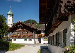 """Der Malerwinkel in Farchant mit der Pfarrkirche St. Andreas und dem Bauernhaus """"Beim Krin"""" ist ein begehrtes Fotomotiv. Das Gebäude ist das älteste Haus in Farchant; der Name geht auf die Familie Krin (1480–1650) zurück. – Foto: Tourist-Info Farchant / Andreas Müller"""
