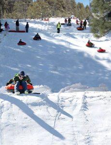 """""""Tubing"""", also mit einem schlauchähnlichen Gefährt den Berg hinunter, zieht im Flagstuff Snow Park besodners Kinder und Jugendliche an. – Foto: Ciscover Flagstaff"""