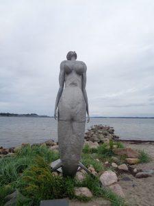 """Die """"Eckernförder Nixe"""", 1999 von Eckhard Kowalke aus Metall hergestellt, steht am Strand von Eckernförde. Die vier Meter hohe Meerjungfrau, die Vitalität und Fruchtbarkeit ausstrahlt, scheint gerade dem Meer entstiegen zu sein und genießt offenkundig Luft und Sonne. In einem sanften Bogen streckt sich ihr ganzer Körper, während die Arme eng anliegen. Eigentlich sollte die Figur im Kurpark aufgestellt werden, doch der Künstler forderte einen Standort direkt am Strand, wo eine Meerjungfrau schließlich hingehöre. Kowalke wurde 1952 geboren, ist seit 1970 freischaffender Künstler und arbeitet in Eckernförde. – Foto: Dieter Warnick."""