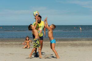 Kinder toben mit ihrem Papa am Strand. – Foto: Mirco Toffolo