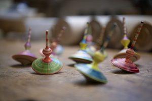 Die Herstellung traditioneller Spielzeuge, wie hier verschieden bunte Holzkreisel, gehören zum Repertoire von Eva Engler. – Foto: Zugspitz Region www.inser-hoamat.de / Christian Stadler